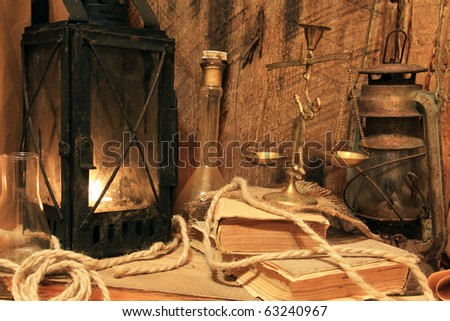 Still life - old lamps, books, balance on wooden background