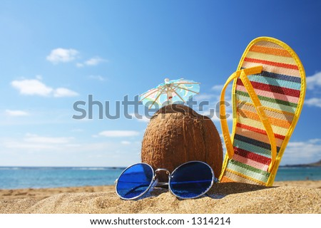 Still life on the beach with sunglasses cocktail in coconut and flip flop
