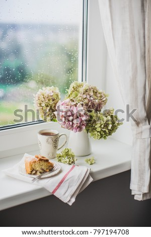 still life on the window - a bouquet of hydrangea in vase and tea with an apple pie #797194708