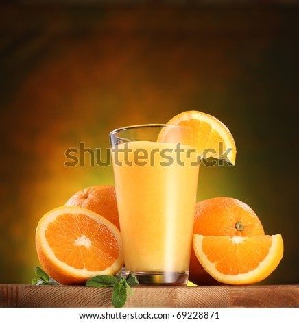 Still life: oranges and glass of juice on a wooden table.