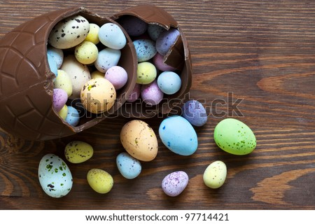 Still life photo of a large broken chocolate easter egg full of mini candy covered eggs in various pastel colours. - stock photo