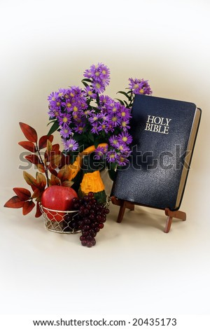 still life photo of autumn foliage, bible and room for copy