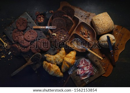 Photo of Still life photography of Bakery and Cookies dark chocolate with dark chocolate and raisins, low key toned image shooting in studio, selective focus and free space for text. Flat lay for advertising.