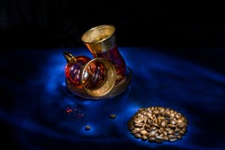 Still life photography with oriental glass caps and coffee beans at the dark blue surface with  light shadow drawing in the dark