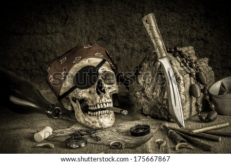 Still life, pirate skull with cigar in the mouth on the log, compass on ancient map, knife brass tea pot and pocket watch