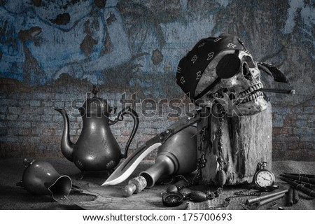 Still life, pirate skull with cigar in the mouth on the log, compass on ancient map, knife brass tea pot and pocket watch with grunge wall background