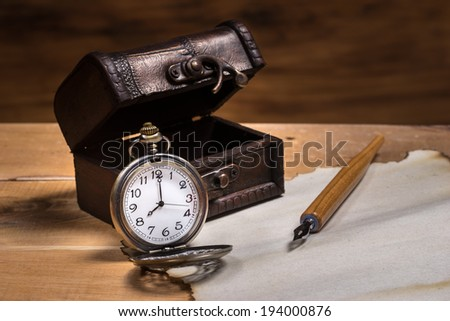 Still life, pocket watch with small leather box and dip pen on burn paper
