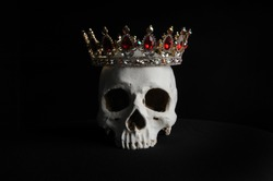 still life portrait of a skull wearing a golden crown, against a black background.