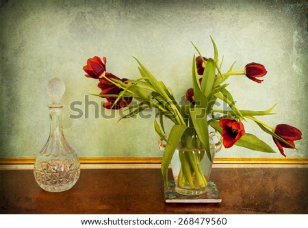 Still life, red tulips in glass vase and decorated glass bottle in interior on grunge vintage background