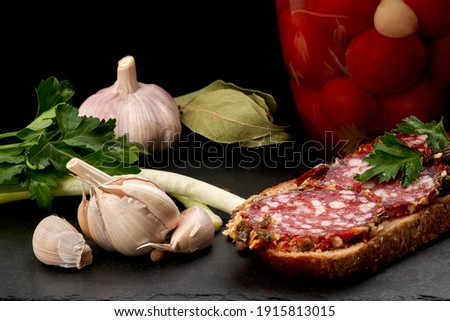 Still life. Sausage sandwich on black bread, head of garlic, onion, parsley, a can of canned cherry tomatoes and bay leaf on a black slate board. Set. Close-up. Foto stock ©