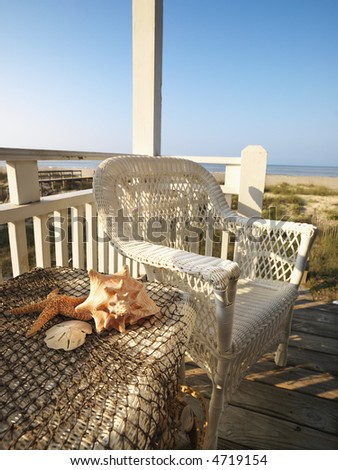 Still life shot of a wicker chair and sea shells on table with beach in background.