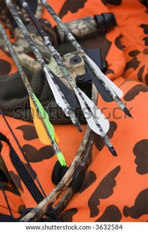 Still life shot of bow and arrows laying against blaze orange camouflage.