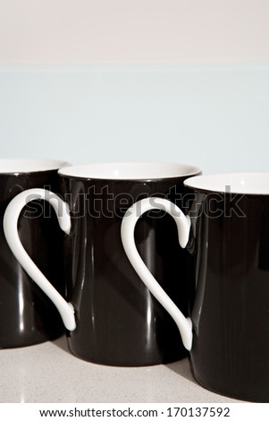 Still life side view of three black and white tea mugs aligned together on a kitchen counter. Home interior coffee drinking detail.