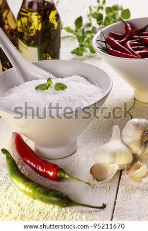 Still life spices:  salt, garlic, peperoni, chillies, chili, oregano - stock photo