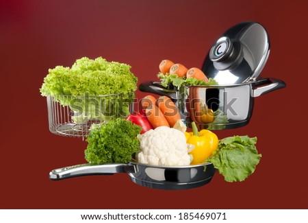 Still Life: stainless steel set of kitchen utensils, on a red background with vegetables and fruit