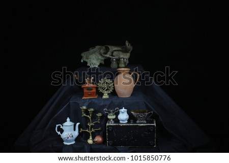 Still life. Still life on a black background. Three-tier still life.  Staging with a skull. Household items in a still-life  #1015850776