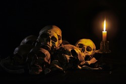 Still life style ;Skulls of bones with Candle flame at night on back background.Halloween day concept.