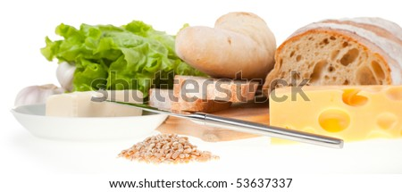still life: table knife, lettuce, bread, cheese, butter and handful of wheat grain in focus
