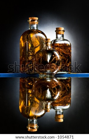 Still life - Three bottles of olive oil and organic herbs