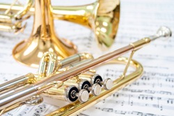 Still life. Three golden trumpets on sheet music. Two lie on the notes and one trumpet stands. Brass Trio.