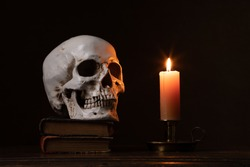 Still life type a scene with human skull and candle