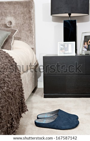 Still life view of an elegant master bed in a design home bedroom with warm colors and fabrics, and a pair of blue slippers resting on the beige carpet floor. Home interior view with no people.