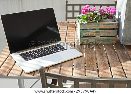 Still life view of open laptop computer on a terrace patio wooden table with decorative flower pot in home exterior area, outdoors. Technology at home and working from home environment with no people.