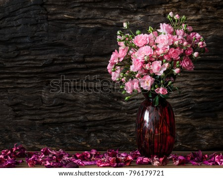 Still life visual art of pink roses arrangement in red glass vase on wooden slap with dry flowers falling round and old wooden back drop #796179721