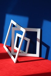 Still life: white square and rectangular frames with shadows on a blue and red background with a wooden texture. Abstract art design composition