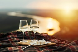 Still life. White wine and cheese. Romantic dinner outdoors at the hill with panoramic view on river. Two glasses, brie cheese on wooden tray. Amazing sunset. Copy space.