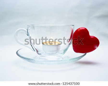 Still life wiht glass cup and red heart and small candle