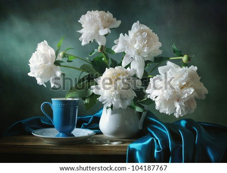 Still life with a blue cup and a bunch of peonies