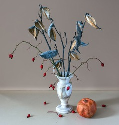 Still life with a bouquet of dried plants, wild rose and ripe pomegranate. Vintage.