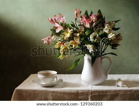Still life with a bouquet of flowers and a cup of tea