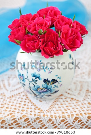 still life with a bright red roses in a beautiful vase