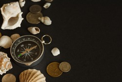 Still life with a compass, coins and shells. Dark background. Nautical theme. Top view travel or vacation concept. Traveler accessories on a dark background with blank space for text. Copy space