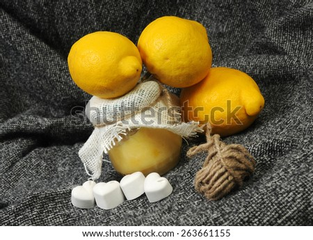 still life with a lemon marmalade jar and bright yellow lemons decorated with chalk hearts and linen on grey background