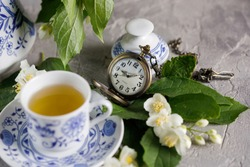 Still life with a magnificent tea set with jasmine flowers and a clock bulb.