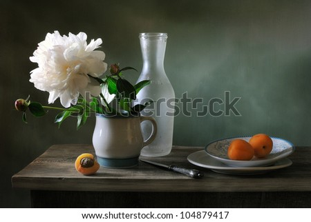 Still life with a peony and apricots - stock photo