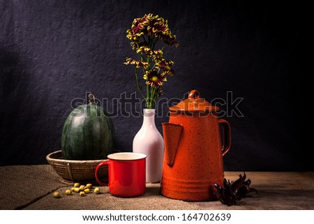 Still life with a red cup and tea pot with a vase of yellow flower