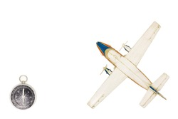 Still life with a scale model of a  plane and compass. Travel concept. Top view travel or vacation concept. Traveler accessories on a white background with blank space for text.