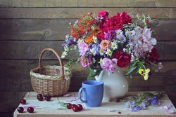 Still life with a summer bouquet with peonies, roses, carnations and other flowers in a white jug and ripe cherries on a wooden table.