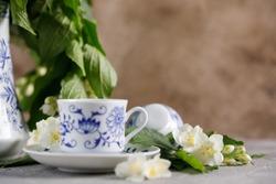 Still life with a tea set and jasmine flowers.