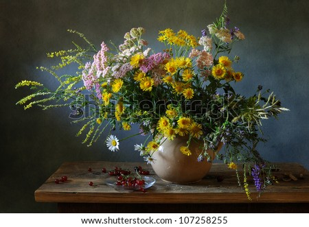 Still life with a voluptuous bunch of field flowers and red currants