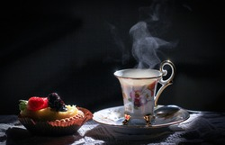 Still life with an old, vintage cup from which steam comes out, which look like a bird, cake with berries, sitting on the table. Surrounded by a dark background
