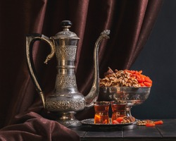 Still life with Ancient East metallic crockery - vintage jug for water or tea, a vase with dried fruit and a plate with tea in armuda glasses.