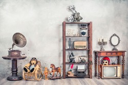 Still life with antique gramophone, old Teddy Bear, toy horse, collection of outdated media devices and writers tools, microscope, desk mirror front concrete background. Vintage style filtered photo