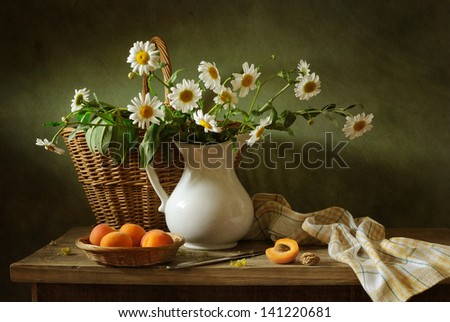 Still life with apricots and camomile flowers