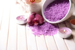Still life with beautiful blooming orchid flower, towel and bowl with sea salt, on color wooden background