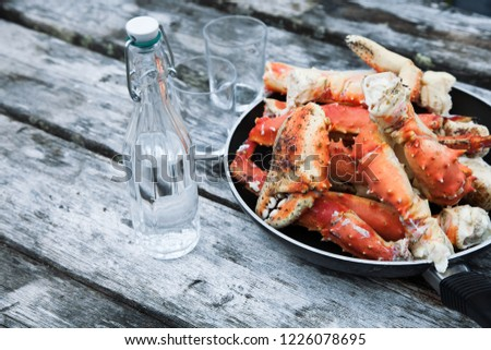 Still life with boiled king crabs and a bottle of vodka on a wooden table #1226078695